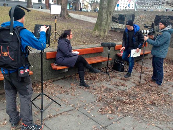 Hr-sjef Birthe intervjues av filmteam i en park