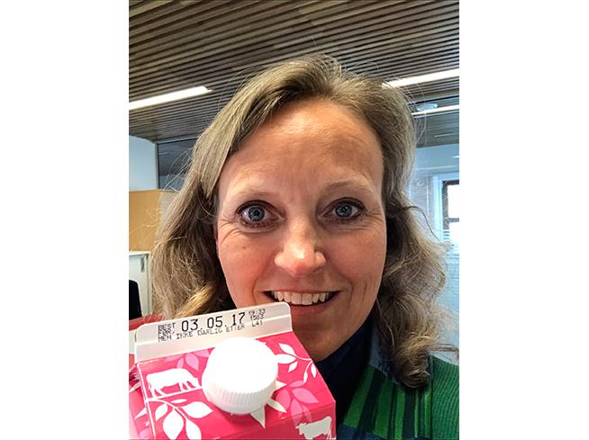 Mette Nygård Havre. Smilende i grønn topp viser frem merkingen på melkekartongen fra Q-Meieriene som viser best før, men ikke dårlig etter