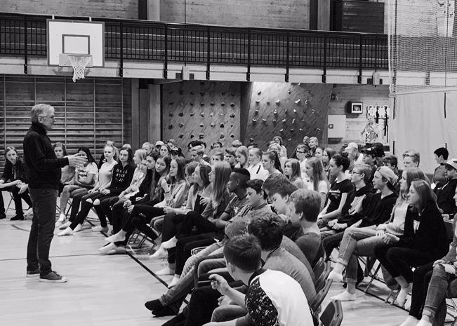 Bent står i en gymsal og snakker med/til en rekke ungdommer som sitter på stoler under en basketballkurv. Innovasjinscamp i Lyehallen. 90 ungomsskoleelever fra Undheim ungdomsskule, Frøyland ungdomsskule og Lye ungdomsskule.