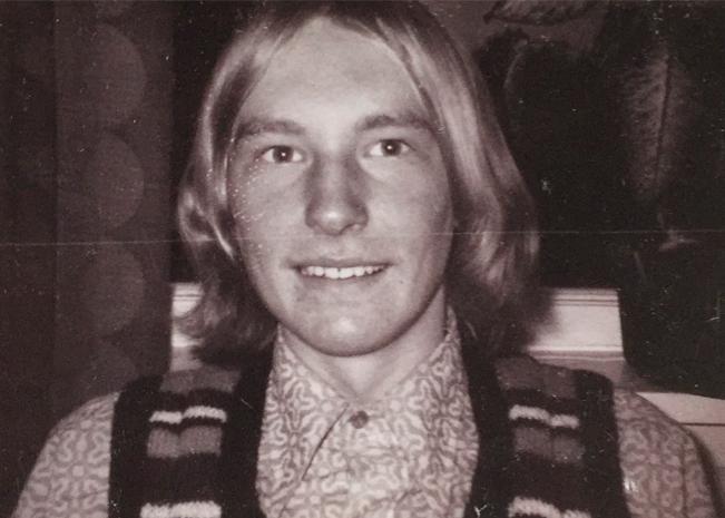 En ung Bent med langt hår, 70-talsskjorte og strikkevest