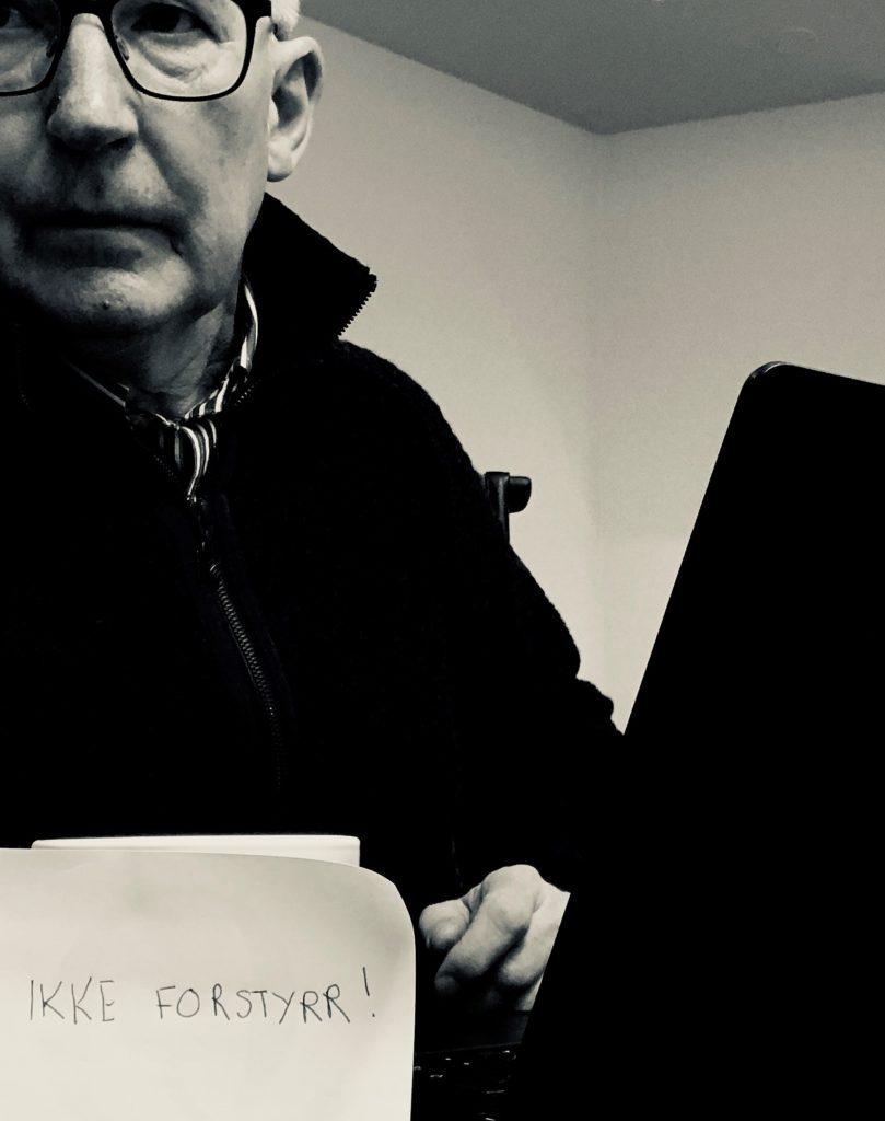 Bilde av Bent foran PC med post-it-lapp som sier ikke forstyrr